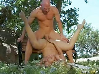 Muscled bald stud drilling busty blond on bench in park