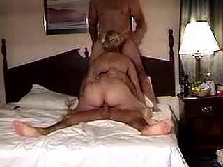 On this group sex private tape, a blonde bitch is having fun with two guys in bed. Bouncing her insatiable moist pussy on one cock, she gives the another one a blowjob.