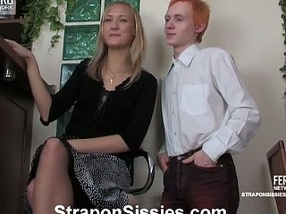 Red-haired lad wears a green dress and a golden-haired wig for a strap-on session