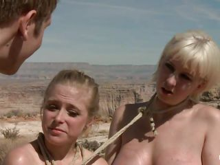 They are in the desert, the burning sun is upon them and made them insanely hot so they fuck like crazy, one chick licks the other ones pussy and gets fucked in the asshole with a dildo. The blonde that is receiving a tongue in her pussy is tied and lays on the sand, will the guy cool her with some sperm?