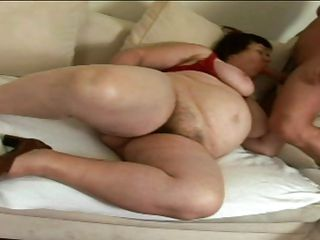 This brunette mom is sitting naked on her sofa and she is fingering her large sexy vagina. She is playing with her enormous breasts too becoming very horny. She is lucky because a guy with a big cock appear and the slut is doing a great blowjob to him. He surely will fuck her hard and deep.