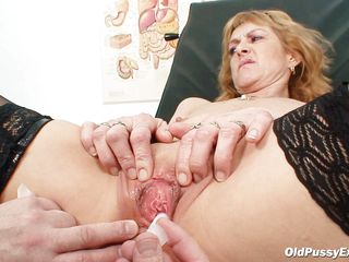 Mature blonde Nora is a slut with big boobs and large shaved vagina that is examined by a gynecologist. The doctor uses a metal speculum and gapes her pussy so we can watch inside it. This slut seems to be healthy and her pussy is now ready for a hard fuck.